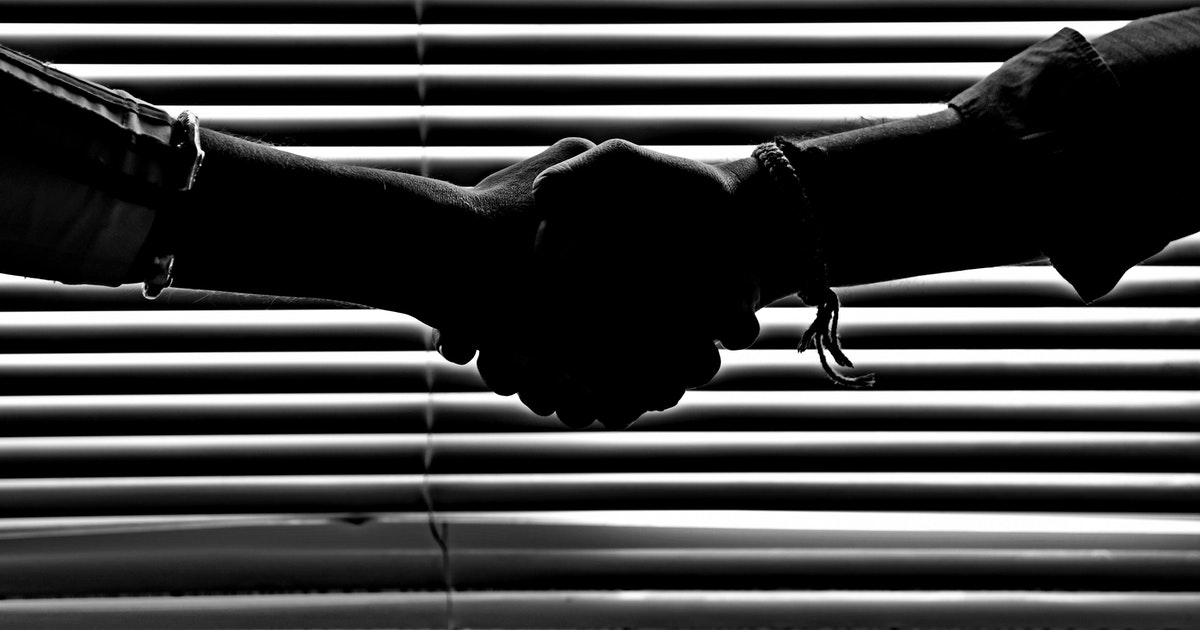 The silhouette of two people shaking hands